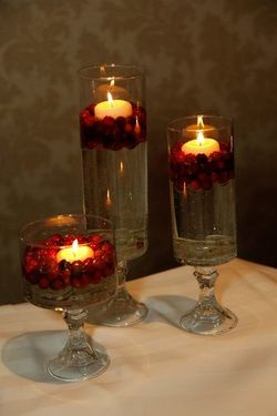 Various size glass vases from Dollar Tree and taper candle holders also from Dollar Tree.Turn the vases upside down and use hot glue to attach the taper holders to the bottom of the vases.On the wedding day, put a few pieces clear glass beads on the bottom and fill with water.  Pour about 1/2 cup of cranberries into each vase and place a floating candle on top.