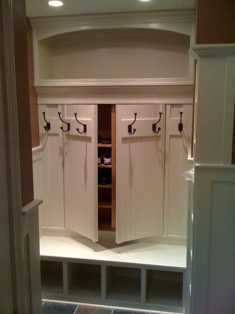 Recessed mudroom storage cabinet with hooks on the doors and a bench in front -- 1