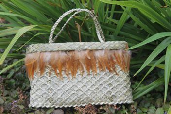This Kete whakairo is authentic, hand woven in traditional maori weaving methods, from NZ Harakeke (Flax).  The handles are made from the flax and the feathers from the Heihei (chicken)  The weaver is a well-known kuia from Te Whanau-A-Apanui.  Constructed strong for everyday use if you so desire.  Each piece is woven with Aroha (Love), a wonderful Koha or accessory for yourself. 100% natural NZ beauty!