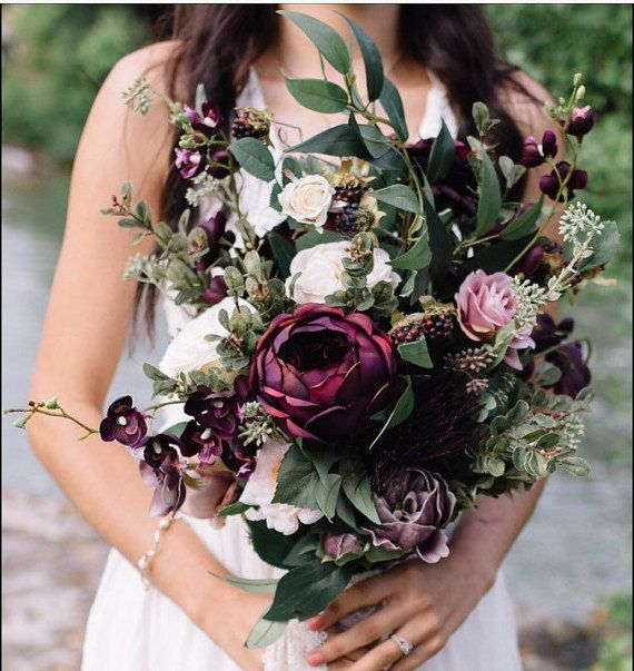 Lush greens, blackberries, dark plum orchids and an assortment of beautiful peonies, roses and other stems fill this stunning bouquet with all the magic of a hike through the beautiful outdoors.