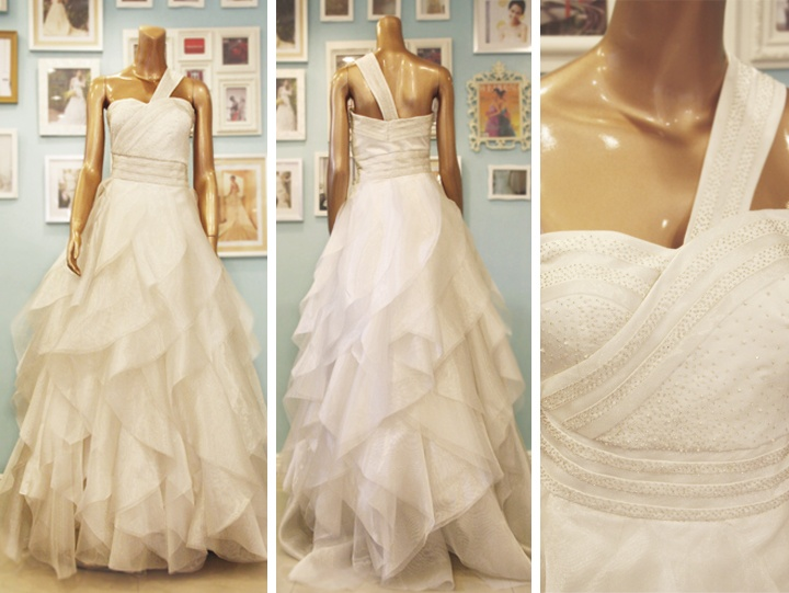 Asymmetrical wedding dress by Camille Garcia with a beaded waist and a tiered skirt made of organza.