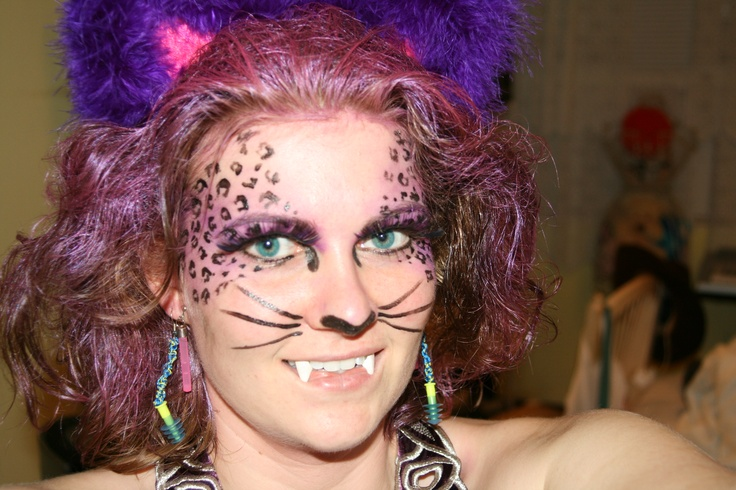 """DIY cat costume. I made the ears with by hot glueing and taping (with electrical tape) cardboard triangles to a plastic headband. Then hot glue felt to the front and back. Line the edge with a strand of marabou feathers. I teased my hair BIG with """"got2b freeze spray""""and covered my head with temporary purple hair spray (party city). The rest is simple face paint and fangs from a costume store (they are super tricky test before hand)"""