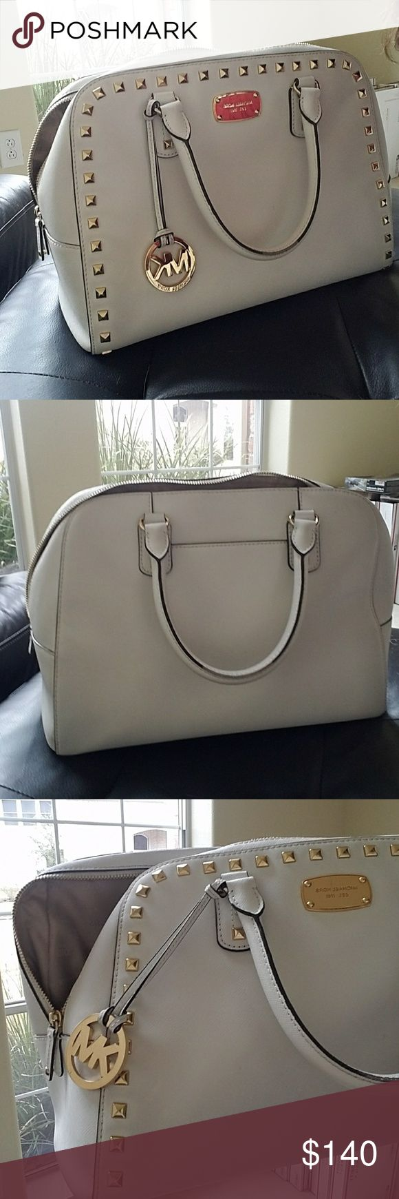 Michael Kors Handbag Off White MK handbag with gold studded detail, name plate and metal dangle. Has an outside pocket for phone storage and 4 small Pockets inside along with the zipper pouch. Pretty clean on the inside aside from a few small spots due to normal use. Outside is very clean aside from a couple of small spots again from normal use Handel's have a little bit of shedding as seen in pic but not noticeable at all and still in great shape. This purse is awesome! Michael Kors Bags…