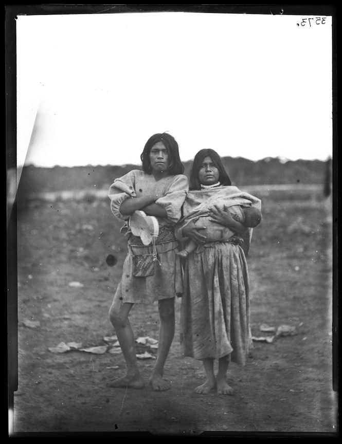 Huichol Indian family, man holding musical instrument, woman holding baby, Mexico, 1895