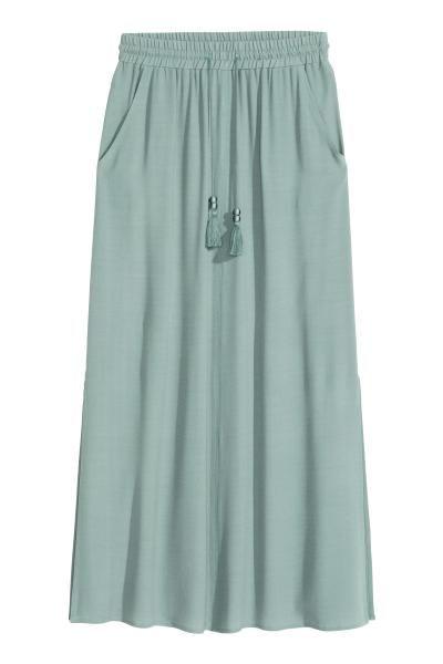 Falda larga: Falda larga en tejido ligeramente arrugado. Cintura elástica con cordón de ajuste y borlas decorativas, bolsillos al bies y aberturas laterales. Sin forrar.