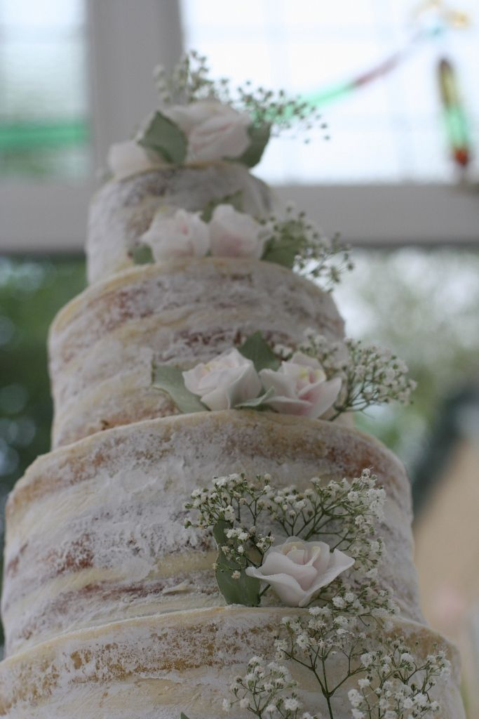 Naked wedding cake with icing sugar coating...@Kandi Rose Matthews I like this instead of totally naked cake because it wouldn't dry out