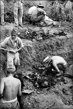 A working party of Japanese POW s excavates  Australian and Dutch  remains from a mass grave at Tarwiri, Ambon, under the direction of Australian war Graves Maintenance Unit, December 1945.       (AWM  03038.06)