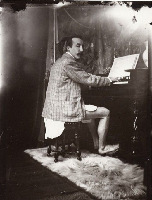 Paul Gauguin playing the harmonium in Alphonse Mucha's studio, Rue de la Grande-Chaumière, Paris, c.1895.