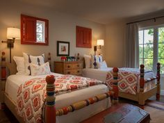 The children's bedroom in the guest house is kitted out with custom-made wooden beds and windows with red shutters. Textiles by John Robshaw, as well as linens designed by Violante & Rochford, are featured throughout the home.