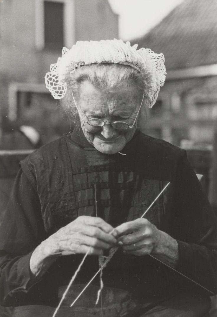 Oude vrouw uit Molkwerum in Friese streekdracht. De vrouw is gekleed in daagse dracht. Ze draagt een gehaakte muts. 1944 #Friesland
