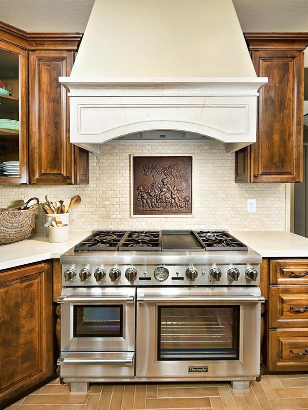 Designer Ellinor Ellefson imported a cherubic early-19th-century iron fireback from Italy for this Mediterranean style kitchen. The arched stove hood enhances the Old Europe feeling. Photography by Bryan Schiele