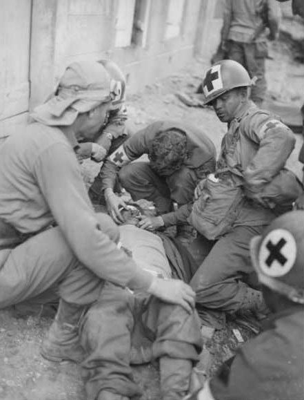 African-American medics of the 4th Armored Division tend to an injured comrade wounded by a German timebomb planted in Coutances. Photo was taken 31 July 1944.