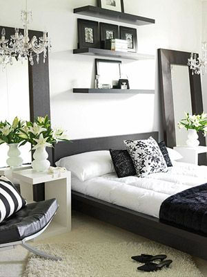 double chandelier, double large mirrors, striped black and white pillow, black throw on the bed, green natural accents