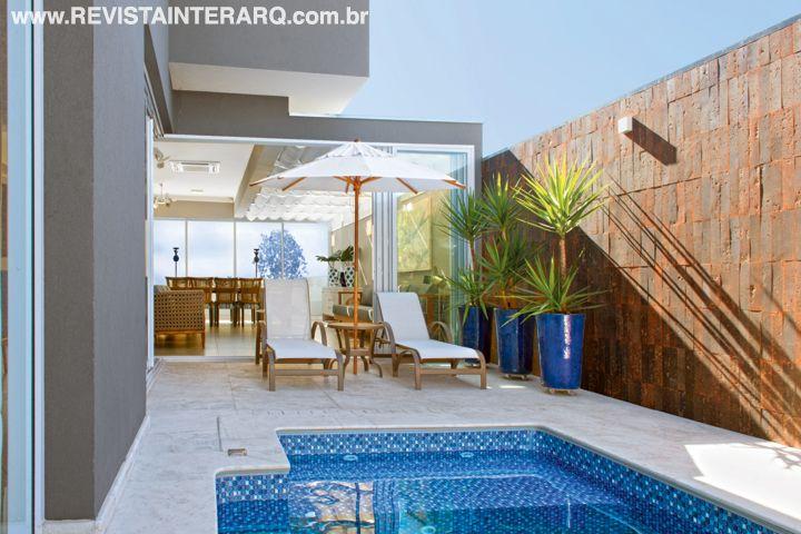 Na piscina, a profissional escolheu revestimento de vinil e piso em mármore branco