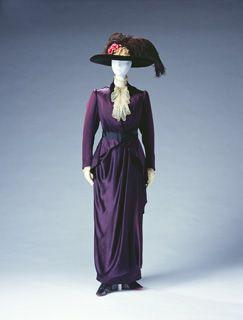 1910 Bulloz day dress- made of soft materials emphasizing feminine charm. Women started wearing tailored suits influenced by men's clothing, in the middle of the 19th century as traveling wear or sportswear.