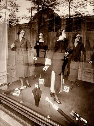 This beautiful and elegant piece is one of Eugene Atget's, his reflected background onto a display of mannequins shows the merging of two elegant worlds, nature and city scape and beauty textiles.