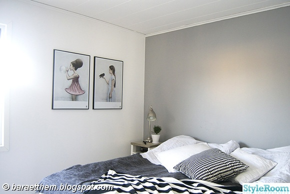 sovrum,tavlor,grå fondvägg,sängbord,sänglampor,filtar,kuddar