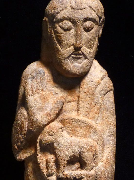 Romanesque limestone figure of Christ, ca. 11th-13th century, free-standing with right hand raised in blessing, holding an orb with the lamb of Christ in his left.