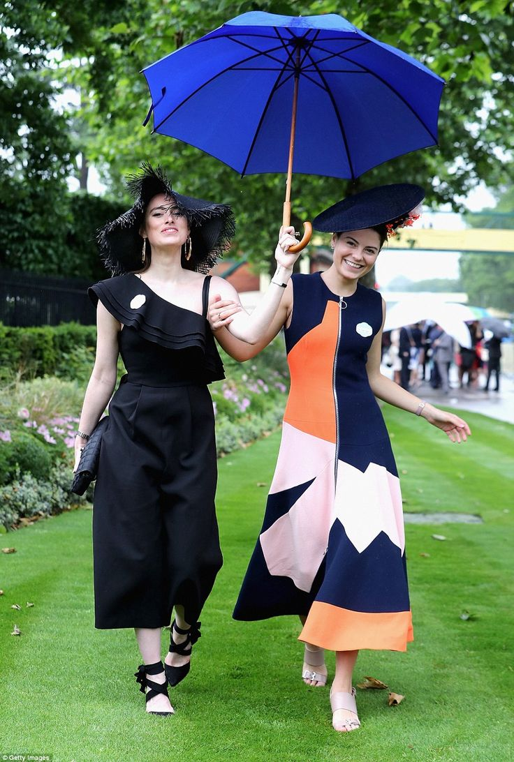 Two racegoers keep dry with a big umbrella as they make their way to the Berkshire racecourse before the drizzle becomes a downpour