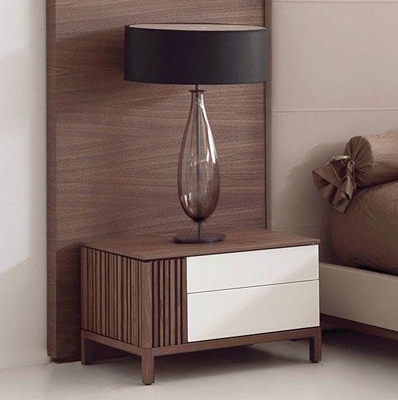 Mesa de noche moderna y combinada con los colores de la cama. Son dos y las encontramos en los dos lados de la cama, que tienen una lámpara cada una.