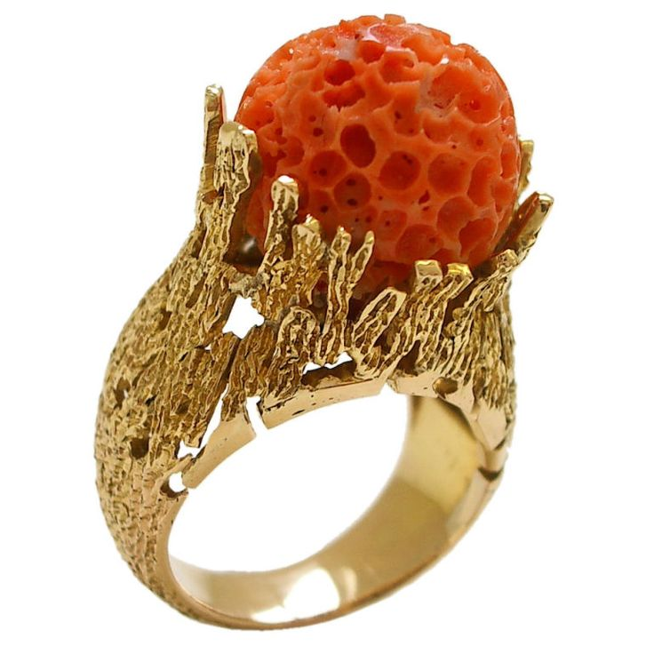 An interesting and unusual 18k yellow gold and natural coral ring. The free-formed textured ring reminiscent of a coral reef, holding a natural coral carved into the shape of a ball