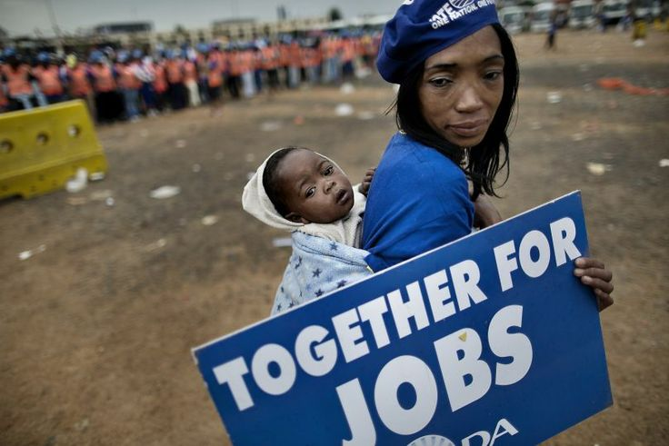 SOUTH AFRICA, Johannesburg : A supporter of the Democratic Alliance, South Africa's main opposition party, holds a placard while carrying her baby as she marches towards the office of the Gauteng province premier in Johannesburg on April 23, 2014 during a protest against corruption and unemployment. South Africa is due to hold general elections on May 7. AFP PHOTO / MARCO LONGARI