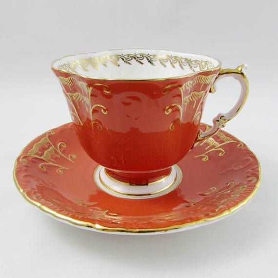 Gorgeous tea cup made by Aynsley. Teacup and saucer are orange with gold decor. Tea cup has a square shape. Gold trimming on cup and saucer edges. Excellent condition (see photos). Markings read: Aynsley England Fine English Bone China For more Aynsley tea cups, please click here: