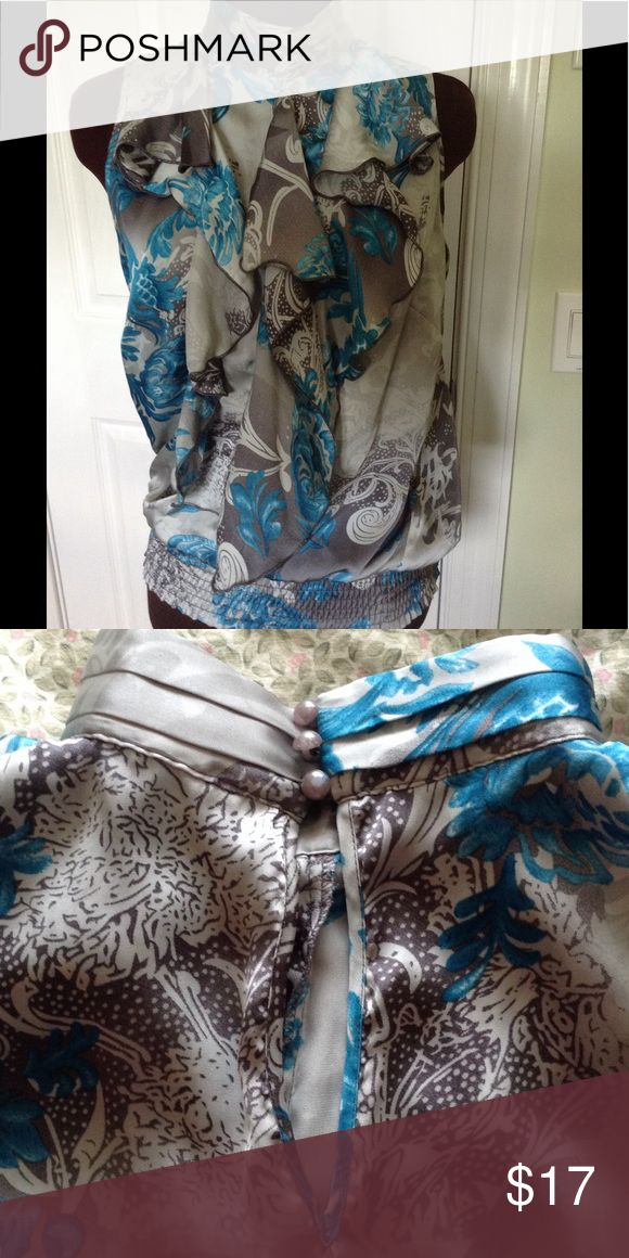 Multicolor sleeveless top with ruffles. This beautiful top has smocked elastic bottom. Satin look and feel to the fabric.  Polyester.  Beautiful floral design in teal, silver and grey. Looks great with grey skirt or pants or white also. Delicate 3 button closure and keyhole back. Dress Barn Tops Blouses