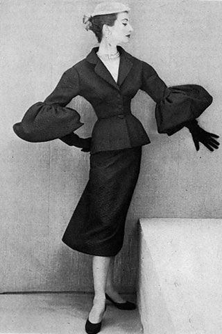 """BALENCIAGA  Puff Piece, Then  As Vogue put it in 1951, this black silk-cloque suit with V collar and quite-straight skirt is """"a quiet buildup for the elegance of the great cuffs.""""     Vogue, 1951  Photo: Henry Clarke / Condé Nast Archives"""