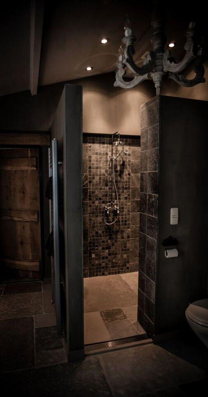 Landelijke badkamer met douche, grijze tegels en chandelier.