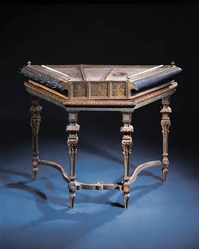 """A DULCIMER Probably 18th Century. Trapeze shaped soundbox with gilt moulding around the edges and finials at the corners, soundbox decorated with musicians and floral motifs set with two gilt roses,  sides decorated with musical trophies, twenty-three courses, one double and twenty-two quadruple with two bridges & two possibly later ivory hammers, on later gilt stand with square tapered legs headed with gilt capitals joined by concave stretchers  30.7/8"""" high; 42.1/8"""" wide; 15"""" deep with…"""