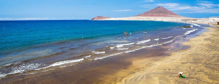 Playa de El Médano Tenerife Sur La playa de El Médano, situada en el municipio de Granadilla de Abona, destaca por la belleza de su fina arena gris y la majestuosa vista del cono volcánico Montaña Roja.  La zona más cercana al pueblo es la más familiar y con menos oleaje. A medida que avanzas por el paseo marítimo encontrarás tiendas de surf, restaurantes y cafeterías, en un ambiente muy cosmopolita