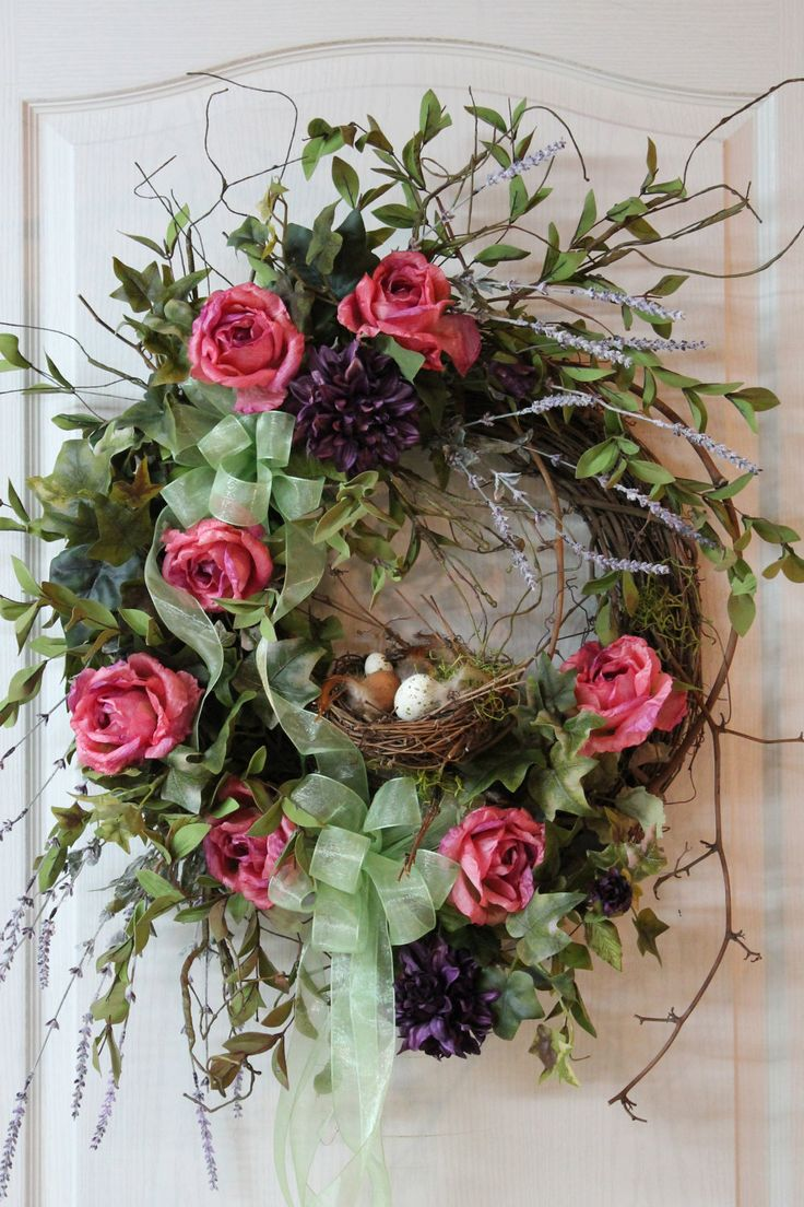 In this beautiful wreath are purple Dahlias, pink Roses with a touch of purple, Lavender, Ivy with a touch of purple, greens, and twigs. A double lime green sheer bow, complements this wreath very nicely! What makes this wreath very unique is the adorable bird nest with five eggs and feathers, sitting on a branch in the middle of the wreath! This wreath will surely brighten your front entrance!