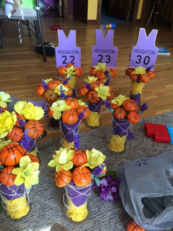 Basketball centerpieces consisting of oranges, fish net, tissue paper, and flowers. Jerseys are made with foam paper, gold jewels, and stenciling using black permanent marker.