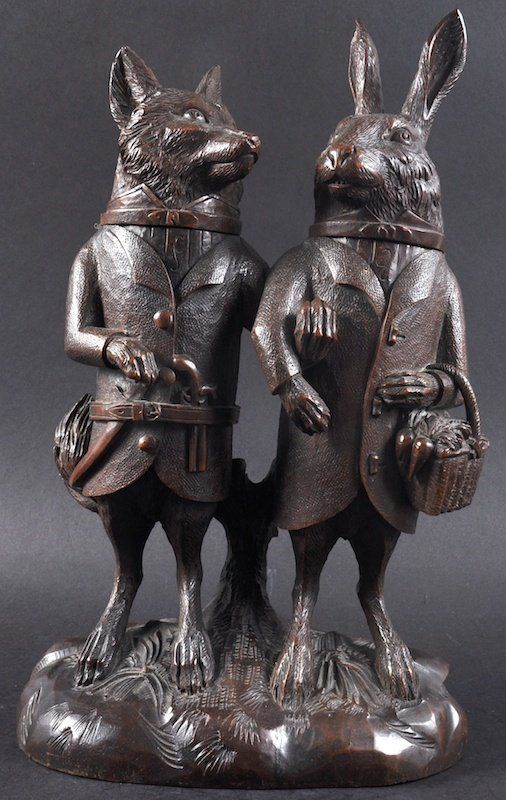 A VERY RARE 19TH CENTURY #BLACKFOREST CARVED WOOD GROUP OF A STANDING FOX AND A RABBIT, each standing side by side, arm in arm, the heads hinged and opening to reveal a compartment for spice etc. 16ins high.