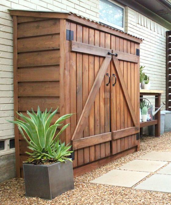 Wood shed attached to fence under carport