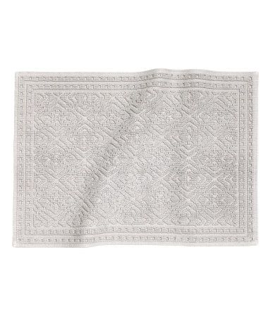 Light gray. Rectangular bath mat in thick, jacquard-weave cotton terry with non-slip protection underneath. Not for use on heated surfaces.