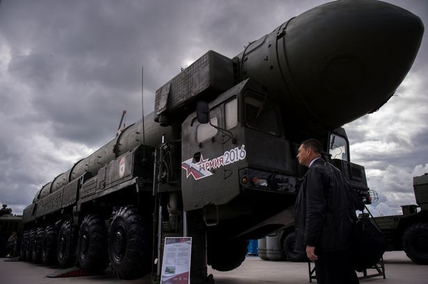 A man looks at a Russian Topol intercontinental ballistic missile launcher at the permanent exhibition of military equipment and vehicles at Patriot Park