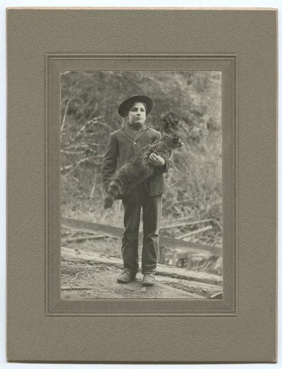 Boy Holding Pet Raccoon.   Etsy.