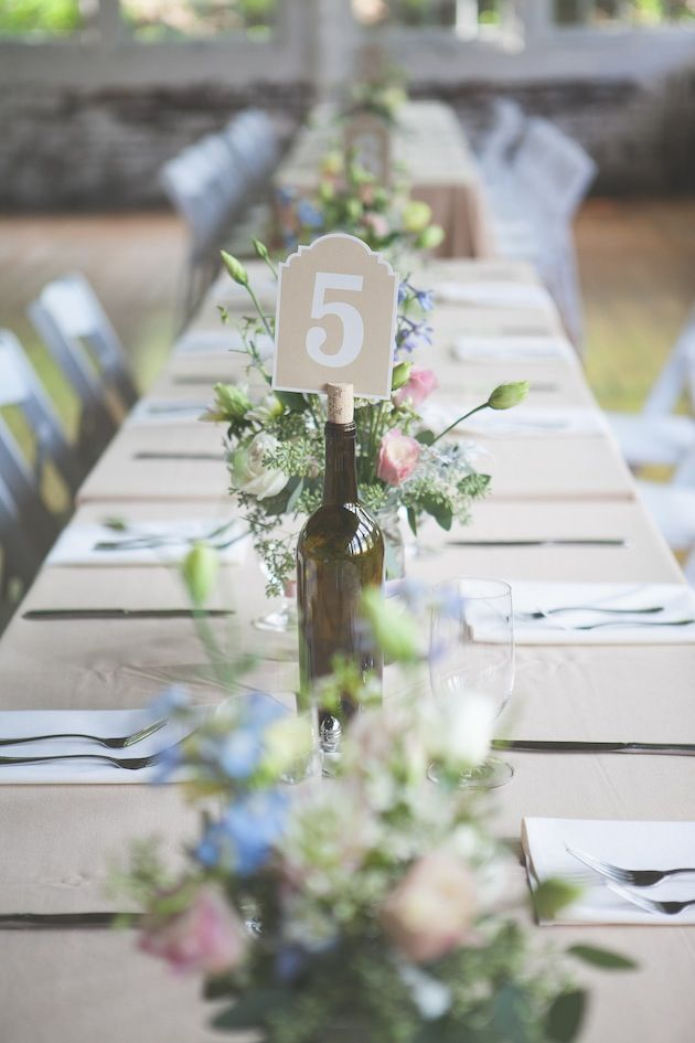 Save money and create a simple, rustic look at your wedding reception by using wine bottles as table number holders!