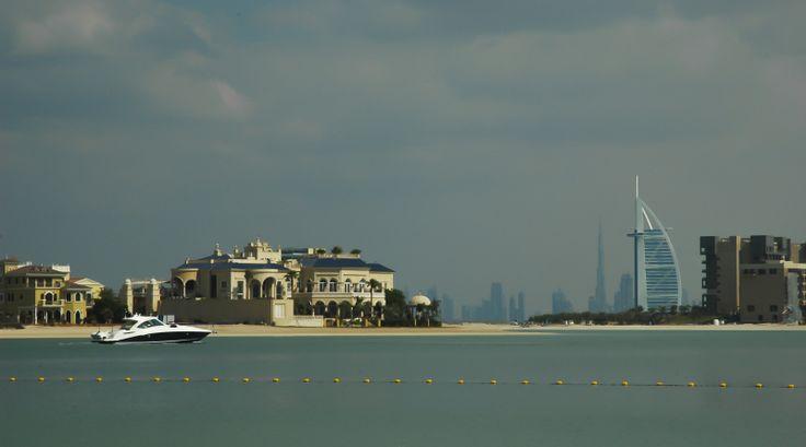 Luxury yacht with Burj Al Arab hotel and Burj Khalifa in the background in Dubai, United Arab Emirates