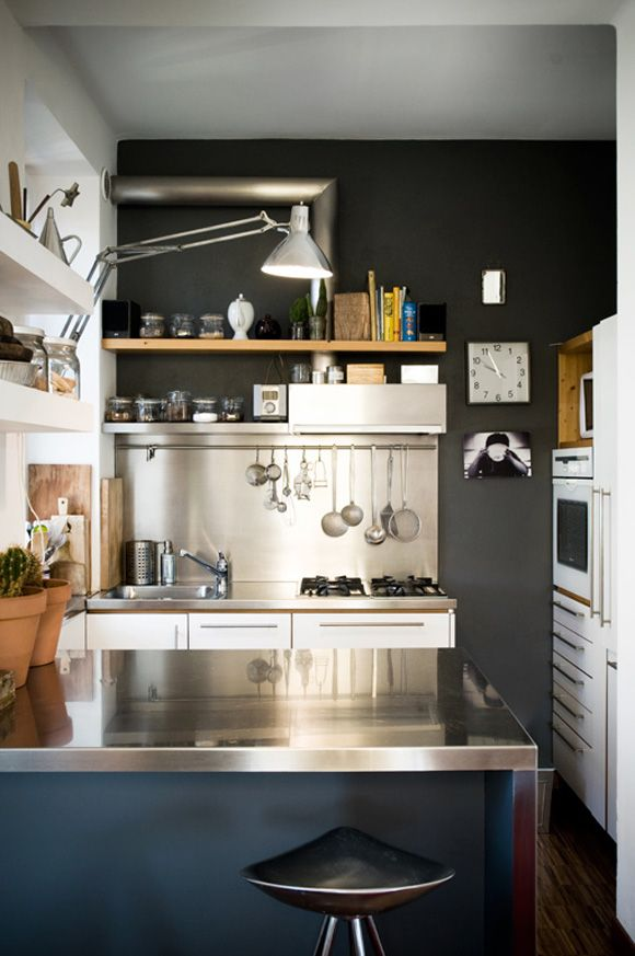 Terrific industrial kitchen done just right. There's a great mix of color, white, wood and stainless; plus that clock and that stool both work so well here.