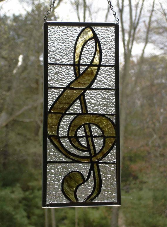Stained glass musical G-clef is constructed of tortoise brown streaky glass and clear textured glass. The frame is a zinc channel and it has a silver chain for hanging.  This unique suncatcher panel will make a great gift for the music lover or teacher.    It is constructed by using the Tiffany copper foil method. Each piece of glass was hand cut, the edges were ground smooth and copper foil was applied to all the edges.It was then soldered together and the channel framing was attached. The…