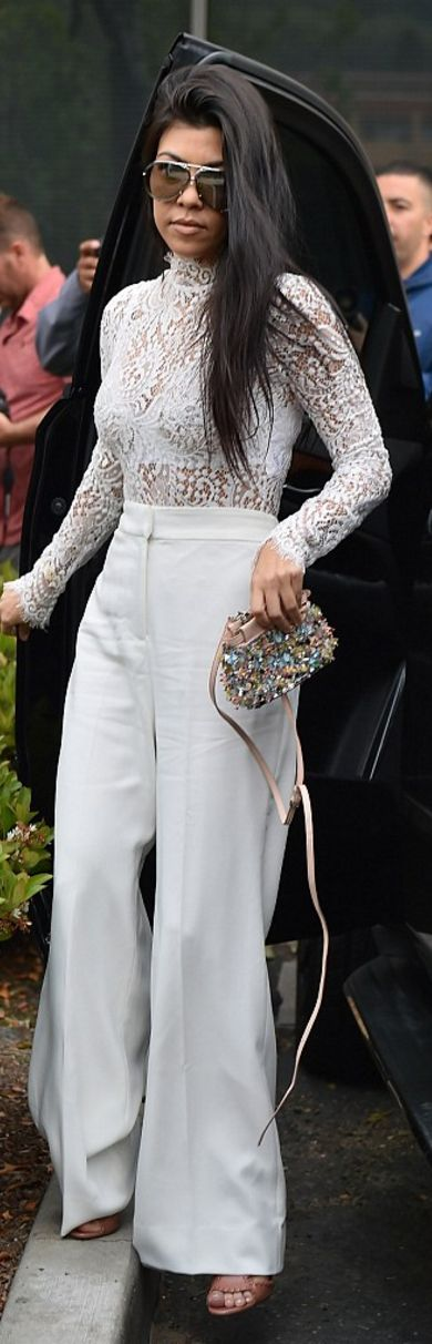 Who made  Kourtney Kardashian's white wide leg pants and beaded handbag?