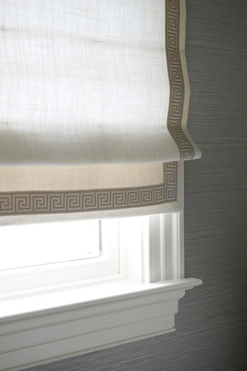 Window molding, grasscloth, roman shade. Gray bathroom features walls clad in gray grasscloth framing a window dressed in a white roman shade with gray Greek key trim.
