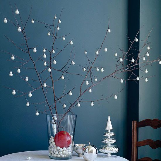 Twinkling, silvery ornaments hanging from winter branches give the appearance of falling snowflakes in this elegant Christmas table decoration. Fill a clear vase with miniature white metallic ornaments and use them to prop up branches. Hang remaining ornaments from branches.