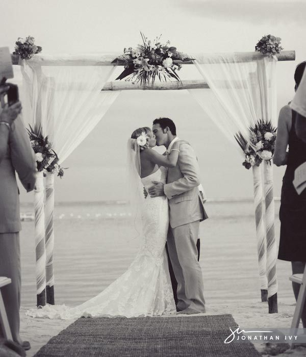 beach wedding arch - ivory tulle and ribbon with green/yellow flowers.  love how the tulle is wrapped around the poles