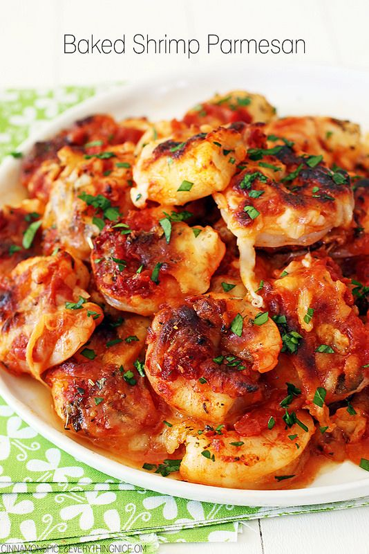 Large shrimp smothered in spicy tomato sauce, mozzarella and Parmesan cheese are drizzled with olive oil and baked in this recipe for Baked Shrimp Parmesan