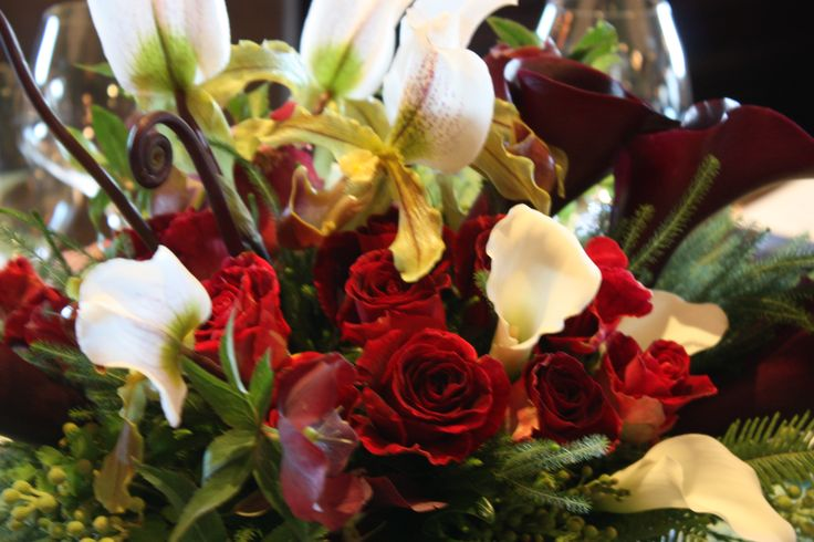 Fern curls, mini calla, deep red roses and Lady Slipper orchids...
