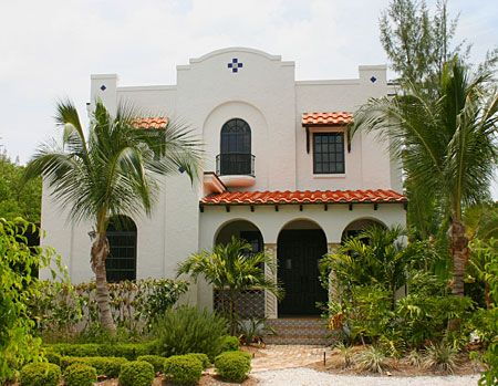 Spanish Colonial Revival (1915 to 1940) features low-pitched red-tile roof, arched windows and doors, shaped parapet, asymmetrical facade, stucco exterior.